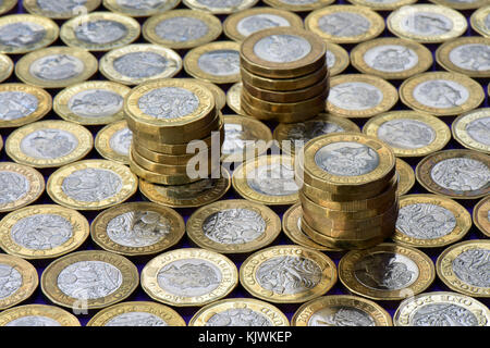 a large number or lots of one pound gold and silver coins lying flat next to each other with stacks or piles of - Stock Photo