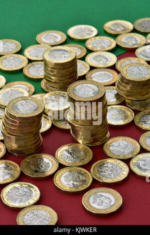 One pound coins from uk currency stacked in piles on top of a scattering of other coins on a red and green background - Stock Photo