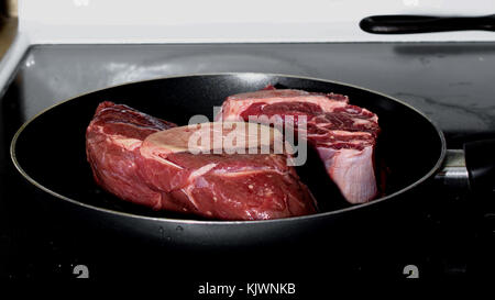 Side view of two raw pieces of meat shank in non-stick frying pan over a stove – cooking read meat concept - Stock Photo