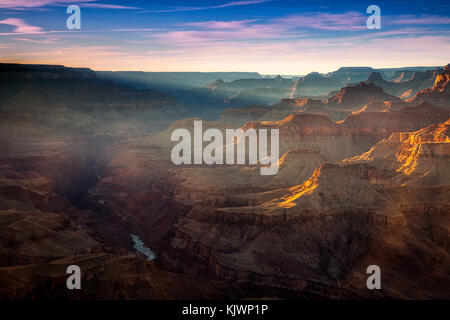 Rays from a setting sun shine down into the Grand Canyon at the Lipan Point overlook on the South Rim - Stock Photo