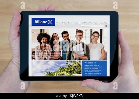 A man looks at the Allianz website on his iPad tablet device, shot against a wooden table top background (Editorial - Stock Photo