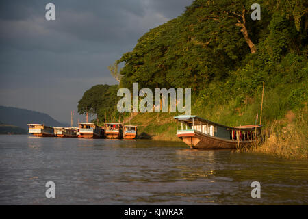 Boats in the evening sun on Mekong river in Luang Prabang - Stock Photo