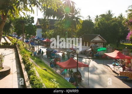 Beginning of the nightmarket in Luang Prabang at sunset - Stock Photo