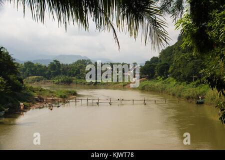 Building of the bamboo bridge over the Nam Khan in Luang Prabang, Laos - Stock Photo