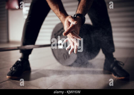 Close-up of a strong man's hands with talc getting ready to weightlifting at the garage gym. - Stock Photo