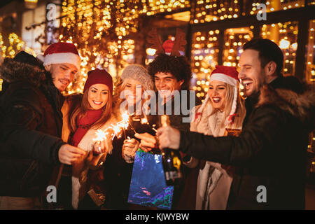 Three couple with sparklers enjoying Christmas outdoor party in the city street at night and with a lot of lights - Stock Photo