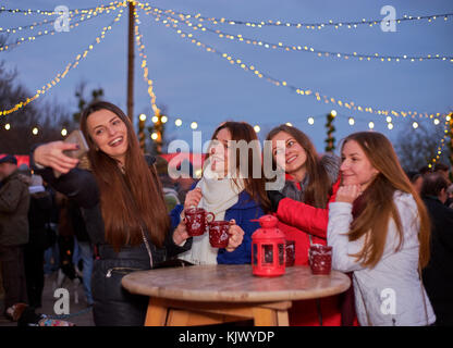 Four young woman making photos at Christmas market - Stock Photo