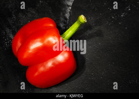 Half cut red bell pepper on a dark slate background, selective focus, space for text. - Stock Photo