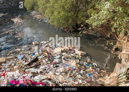 Plastic bags, household waste and sewage create heavy pollution in river at Juhu, Mumbai - Stock Photo