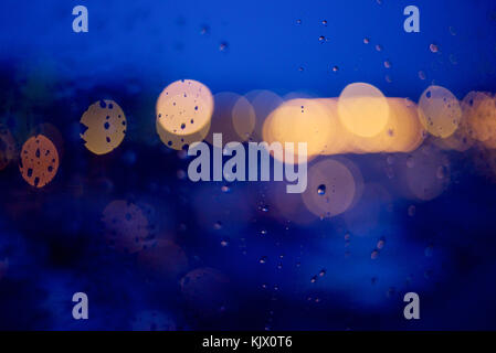 View through a window at night with raindrops and bokeh effect on lights - Stock Photo