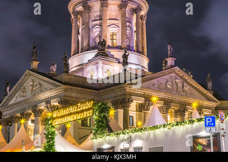 View over the Christmas Market 'Weihnachtszauber Gendarmenmarkt' with the illuminated New Church (Deutscher Dom) - Stock Photo