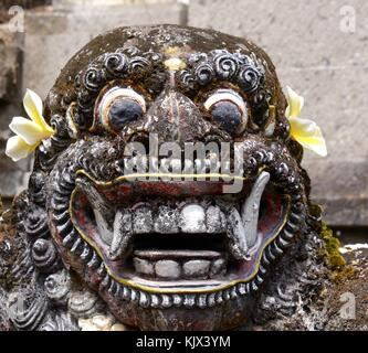 Close up of grotesque, scary face of statue of Balinese demon with staring eyes and fangs at Pura Sangara sea temple - Stock Photo
