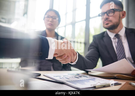Confident bearded entrepreneur wearing elegant suit sitting at boardroom table and greeting business partner with - Stock Photo