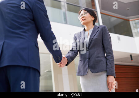 Portrait of confident Asian entrepreneur standing in spacious office lobby and greeting her business partner with - Stock Photo