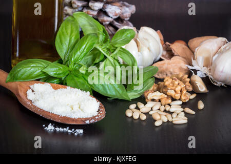 Ingredients for making green pesto sauce homemade with basil and pine, nuts, cheese,garlic in dark wood table background. - Stock Photo
