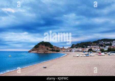 Beach in resort town of Tossa de Mar on overcast cloudy day, Costa Brava, Catalonia, Spain - Stock Photo