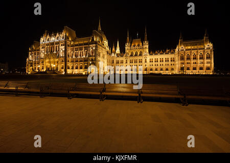 Hungarian Parliament lighted at night in Budapest, Hungary, alley with benches on Kossuth Lajos Square - Stock Photo