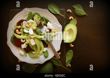Healthy beet salad with fresh sweet baby spinach, nuts, feta cheese and avocado. Plate with salad on dark table. - Stock Photo