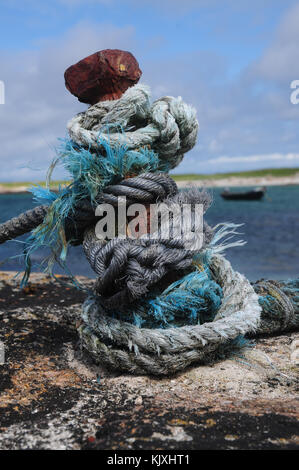 Knotted rope on an iron stanchion on a harbour with traditional Irish Curragh in the background - Stock Photo