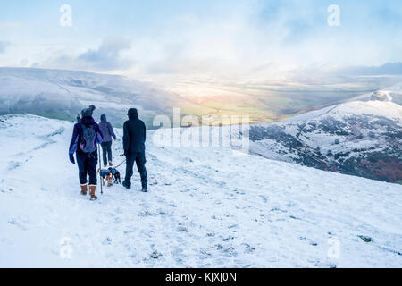 Winter walking. Hill walkers with dogs in the snow on The Great Ridge, with sunshine in the distance. Derbyshire, - Stock Photo
