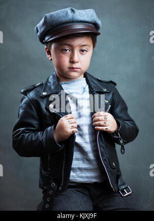 Handsome multiracial Asian Caucasian little boy wearing a black leather motorcycle jacket from the movie The Wild - Stock Photo