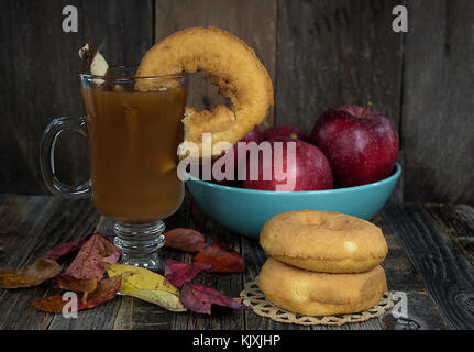 donut on edge of apple cider in glass mug with fall leaves and red apples in turquoise bowl on rustic wood - Stock Photo