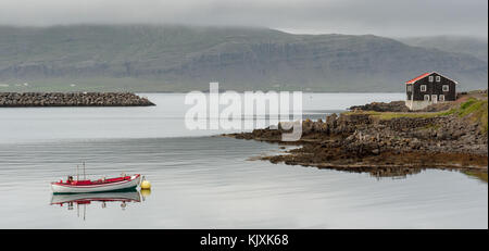 Red and white fishing boat anchored in front of a wooden house in Djupivogur harbor, South Iceland - Stock Photo