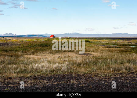 A small red-roofed hut lost in the middle of a desert landscape in Iceland's wilderness - Stock Photo