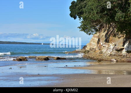 Marginal oceanic surf on flat beach with rocky cliff on th side. - Stock Photo