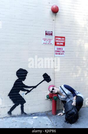 NEW YORK, NY - OCTOBER 20:  The latest work from street artist Banksy. Banksy is a pseudonymous England-based graffiti - Stock Photo