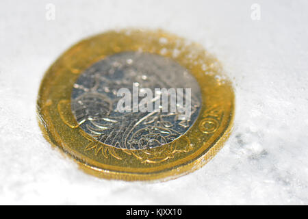 New One Pound coin frozen in ice - Stock Photo