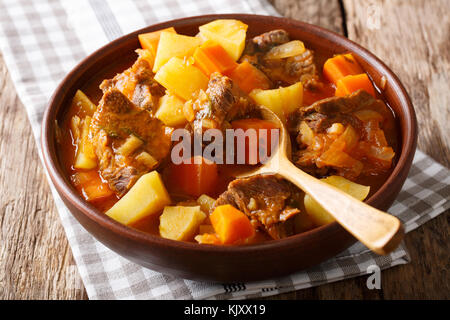 Braised beef Estofado with vegetables close-up in a bowl on the table. horizontal, rustic - Stock Photo