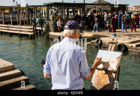 An unknown artist paints the scene as travellers leave a Vaporetto (Water Bus) stop beside Ponte della Paglia in - Stock Photo