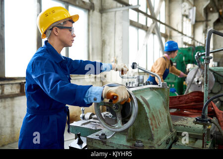 Concentrated confident engineer working on tailstock and rolling wheel in factory workshop - Stock Photo