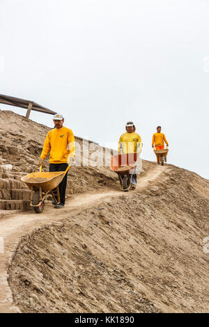 Three local Peruvian workmen with wheelbarrows working on restoration of the pre-Inca ruins at Huaca Pucllana or - Stock Photo