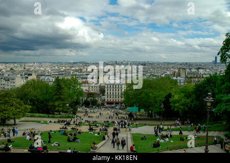 Looking into Paris from the Mantmartre summit with tourists walking up the hill to visit the Basilica du Sacre-Coeur - Stock Photo
