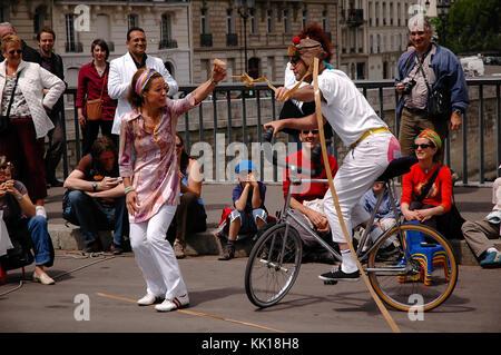 Street performer entertain tourists on the The pont Saint-Louis bridge across the River Seine beside Notre-Dame - Stock Photo