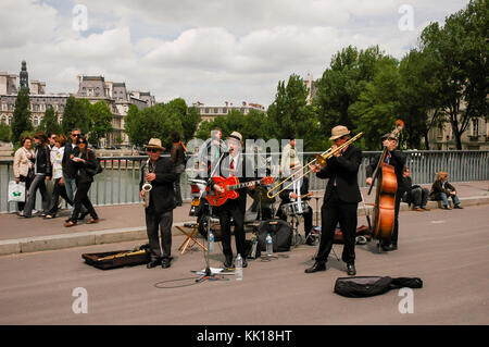 Jazz band entertains tourists on the The pont Saint-Louis bridge across the River Seine beside Notre-Dame Cathedral - Stock Photo