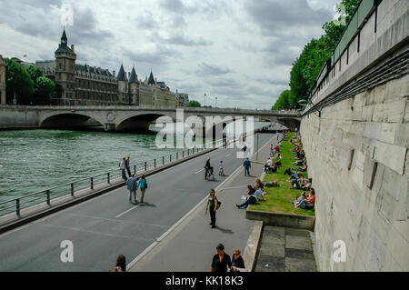 Tourists relaxing on the banks of river Seine with view on The Pont au Change bridge and the Conciergerie Fortress - Stock Photo