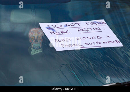 Do not park here again road closed & parking suspended - hand written note with misspelling on car windscreen at - Stock Photo