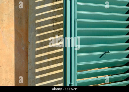 green painted shutter with shadow on house wall, florence, italy - Stock Photo