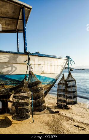Oyster farming cages hanging from a boat on the sand at Santo Antonio de Lisboa Beach. Florianopolis, Santa Catarina, - Stock Photo