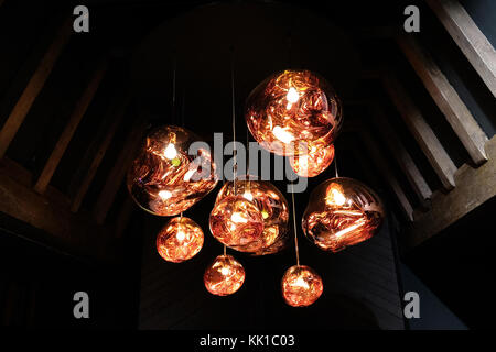 Tom Dixon copper colour 'Melt' pendant lights hanging in the Liberty of London store, London UK. Photographed November - Stock Photo