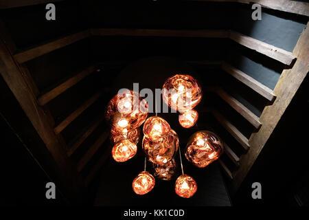 Tom Dixon copper colour 'Melt' pendant lights hanging in the Liberty of London store, London UK. Photographed November - Stock Photo