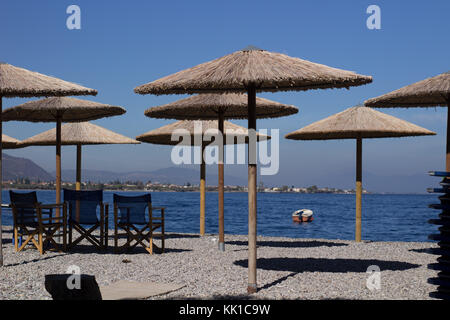 empty beach umbrellas in a row with chairs  on an autumn sunny scenic day - Stock Photo