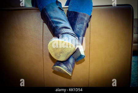 Crashed out on the sofa, long day, exhausted just like the old boots - Stock Photo