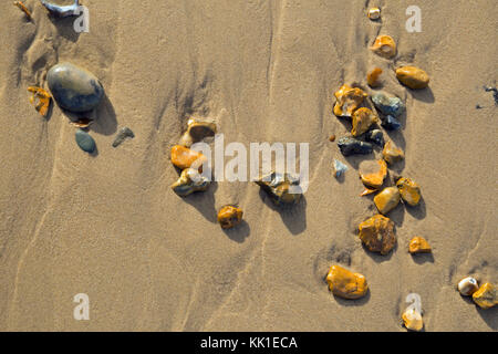 Pebbles left by the tide on a sandy beach, viewed from above and photographed in landscape format. - Stock Photo