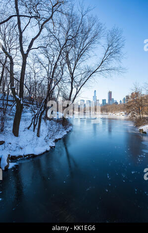 Wintry view of Central Park from the frozen lake with the urban skyline of the Upper West Side in Manhattan, New - Stock Photo