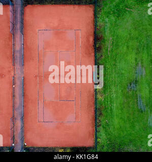 Tennis court with red gravel next to a lawn, abstract effect by vertical aerial photograph with drone - Stock Photo