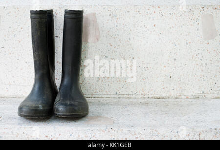 Black rain boots on marble garden bench - Stock Photo